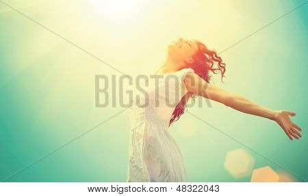 Free Happy Woman Enjoying Nature. Beauty Girl Outdoor. Freedom concept. Beauty Girl over Sky and Sun. Sunbeams. Enjoyment.