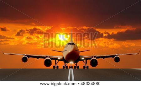 Airplane takeoff on runway at sunset
