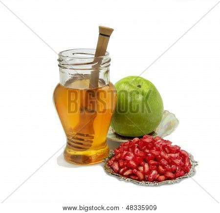 Honey, apple and pomegranate on white