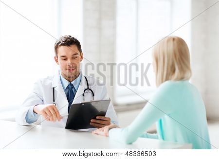 healthcare and medical concept - male doctor with patient in hospital