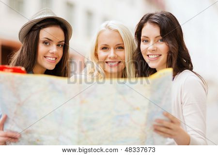 holidays and tourism concept - beautiful girls looking into tourist map in the city