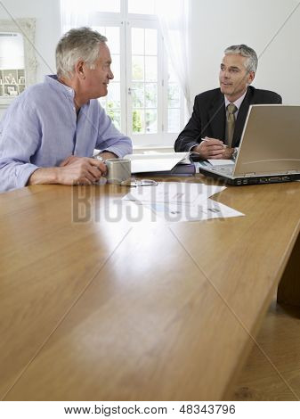Mature man sitting at table with financial advisor