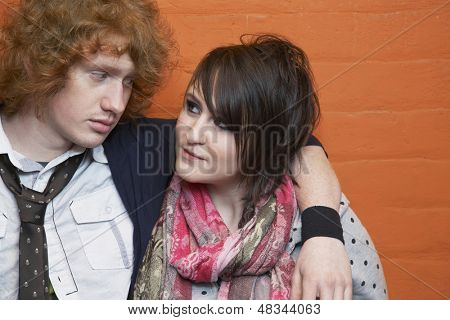 Closeup of young couple with arm around looking at each other against orange brick wall