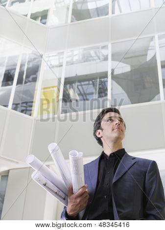 Low Angle View of ein Unternehmer holding gerollt Blaupausen unter Arm im Atrium des Office building