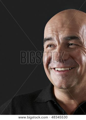 Closeup of bald middle aged man smiling on black background