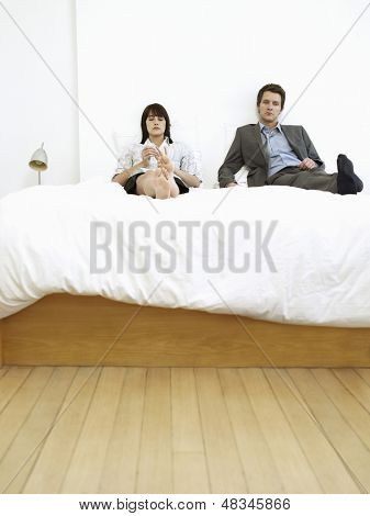 Young business couple sitting on bed, ignoring