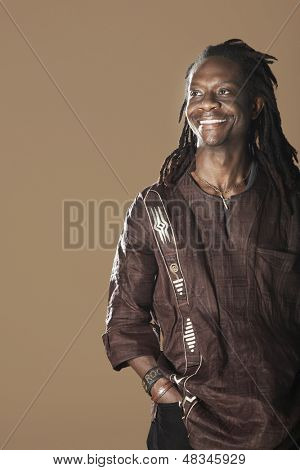 Portrait of smiling African American man with dreadlocks looking away on brown background