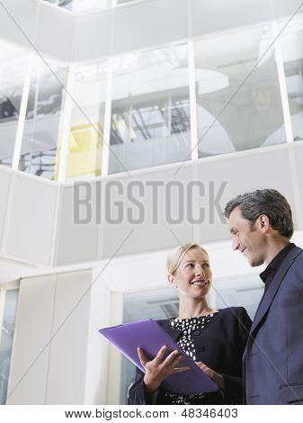 Low Angle View of zwei lächelnd Geschäftsleute mit einem Ordner im Büro-atrium