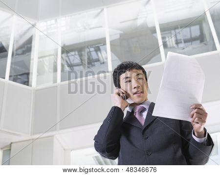 Kaufmann mit Handy im Atrium des Office building