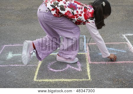 Side view of young girl playing hop-scotch in playground