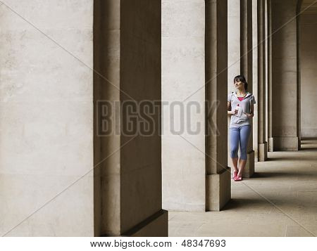 Full length of a young woman standing against column in portico