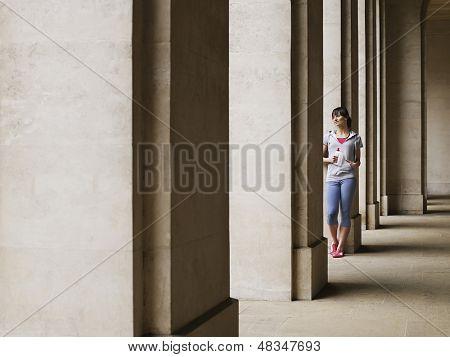 Voller Länge einer jungen Frau, die ständigen gegen Spalte im Portikus