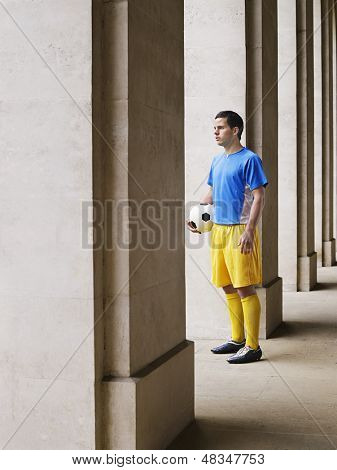 Voller Länge eines Fußballspielers holding Ball im Portikus