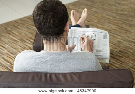 Rear view of a young man sitting on sofa and doing crossword puzzle in newspaper
