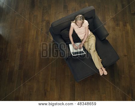 Top view of a middle aged woman sitting on sofa and using laptop