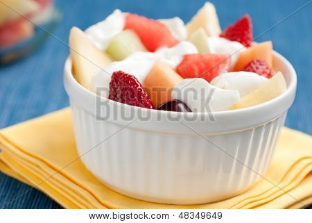 A studio shot of Greek yogurt, fresh strawberries, cantaloupe, melon, pineapple, and grapes in a white bowl on a bight blue tablecloth and yellow napkin.