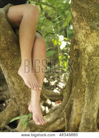 Closeup lowsection of a young woman sitting on tree branch with barefeet