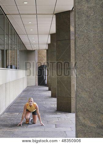 Voller Länge eines weiblichen Athleten hockend in Ausgangsposition auf Pflaster von Säulen im Portikus