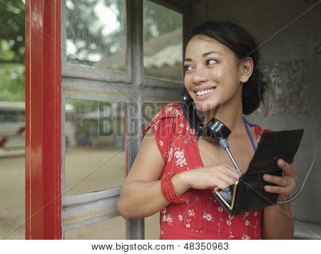 Happy young mixed race woman using public phone while looking away
