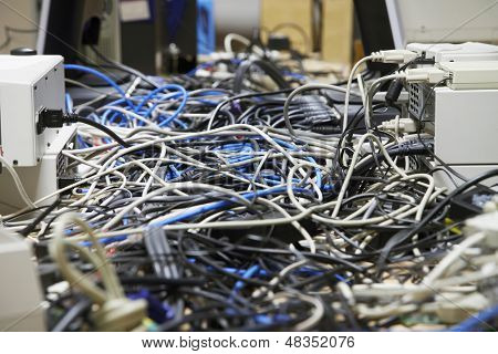 Closeup of messed wires connecting computers and printers in office