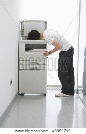 Full length side view of a man putting his head in copy machine in office hallway