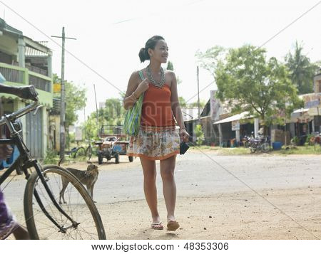 Full length of a smiling young mixed race woman walking on dirt road