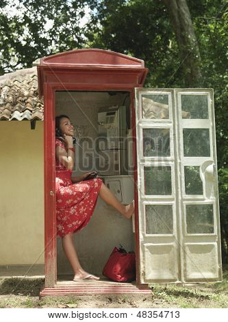 Full length side view of a young woman using pay phone