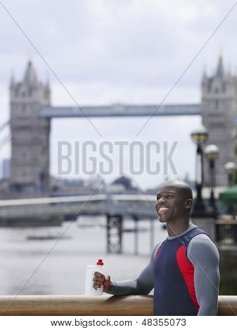 Smiling young African American man with water bottle in front of Tower Bridge in England