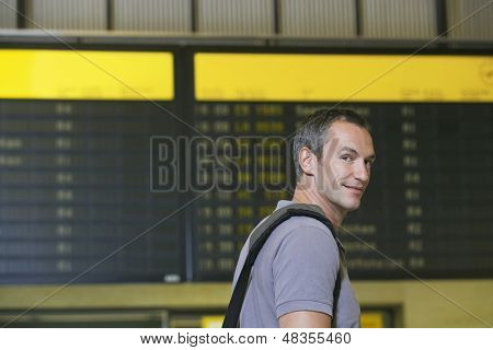 Closeup of a smiling male traveler in front of flight status board in airport