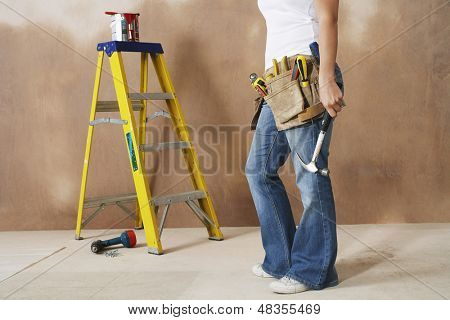 Lowsection of a woman with toolbelt and hammer leaning against wall