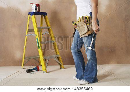 Lowsection einer Frau mit Hammer an die Wand gelehnt und toolbelt