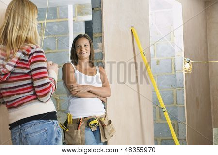 Young woman with toolbelt talking to a female friend