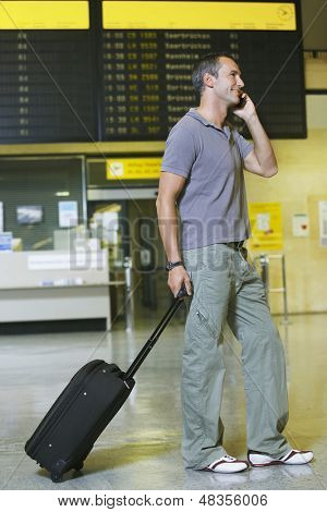 Full length side view of a male traveler using mobile phone in front of flight status board in airport
