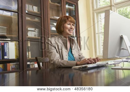 Smiling middle aged woman using computer in study room at home