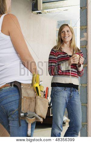 Zugeschnittenen Frau mit Toolbelt reden zu einer lächelnden jungen weiblichen