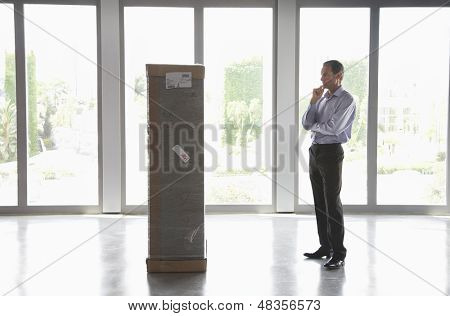 Full length side view of a man with hand on chin observing package in empty office