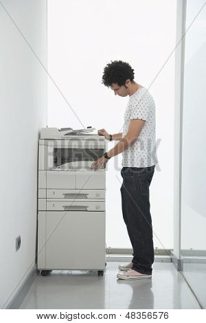 Full length side view of a young man using copy machine in office hallway