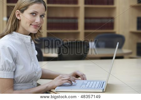Side view of a smiling female office worker using laptop in legal office