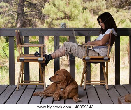 Woman relaxing with laptop and dog