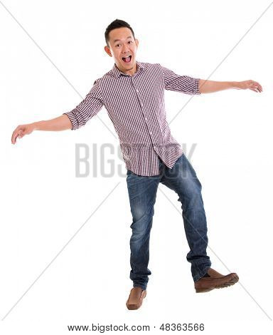 Full body Asian man walking carefully, try to balance himself, isolated on white background. Asian male model.