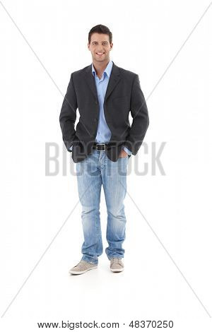 Casual portrait of young businessman, standing with hands in pocket, smiling at camera, isolated on white.
