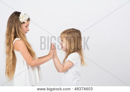 Two little girls dressed in white playing slapping each others hands