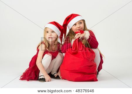 Two girls in a red dress in the bell Santa Claus sitting with a bag of gifts