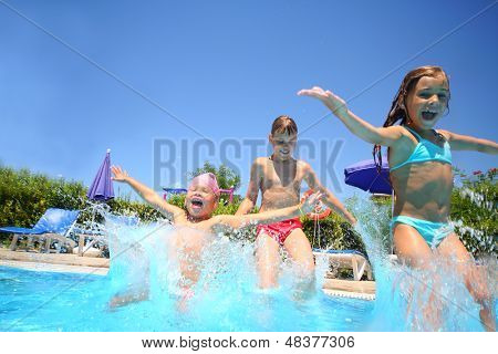Two little girls and boy fun jumping into the swimming pool, shot through the underwater package