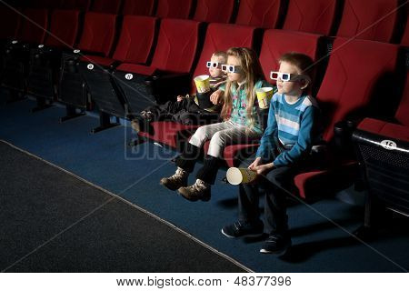 A boy with sister and small brother in 3D glasses watching a movie on the front row of the cinema
