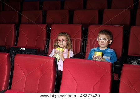 Little boy and girl with round glasses with popcorn watching a movie