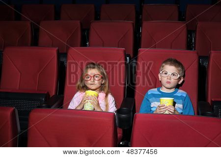 Little boy and girl with round glasses eating popcorn and watching a movie carefully