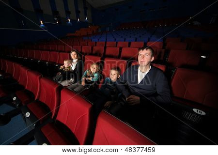 Father and mother with their children watching a movie in the cinema