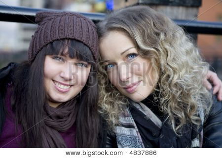 Attractive Embracing Girls Sitting On The Bridge