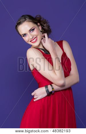 portrait of a cheerful young woman in red evening dress and upstyle hairstyle against purple studio background